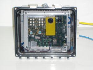 Bild 1: Die ToF-Kamera in wasserfestem Gehäuse: Der 3D-Sensor verbirgt sich hinter dem gelben Block unter dem Bandpassfilter, links oben sind zwei LED-Emittermodule. (Bild: VoXel Interaction Design)