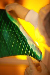 Dünn, leicht und biegsam: Die Firma Heliatek dampft einen fotoaktiven Film hauchdünn auf eine Trägerfolie auf. Die Folie kann somit nahezu unbegrenzt zur Stromproduktion eingesetzt werden. (Bild: Heliatek / Tim Deussen, Berlin)