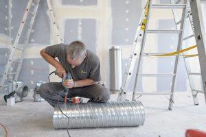 Ein Wisag Mitarbeiter bohrt Löcher für die Montage von Zu- und Abluftrohren (Bild: Wisag Industrie Service Holding GmbH)