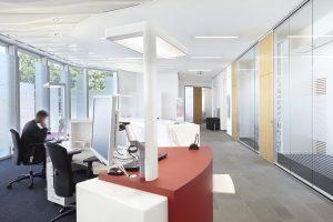 ((Die blendfreie Technik der LED-Hybrid-Leuchte Opura verhindert eine Lichtspiegelung auf den schirmen und eignet sich daher besonders gut für PC-Arbeitsplätze. Ein Schreiner integrierte die Leuchte direkt in den Beratungstresen.)) (Bild: Zumtobel Lighting GmbH)