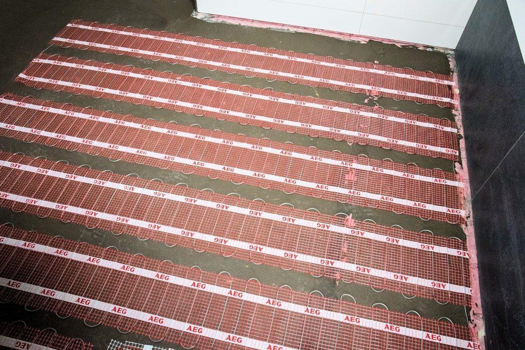 Durch das flexible Trägergewebe und die geringe Aufbauhöhe der Heizmatte (3mm) eignet sich die Fußbodenheizung für jegliche Anforderung. (Bild: AEG Haustechnik GmbH)