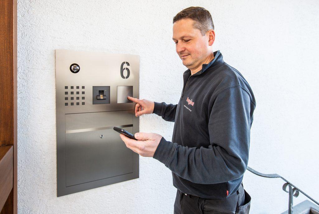 Elektroniker Miroslaw Koziol prüft den Türruf, der über die Siedle App auf dem Smartphone ankommt. Die Türstation ist im rechten Winkel zur Haustür verbaut. (Bild: S. Siedle & Söhne)