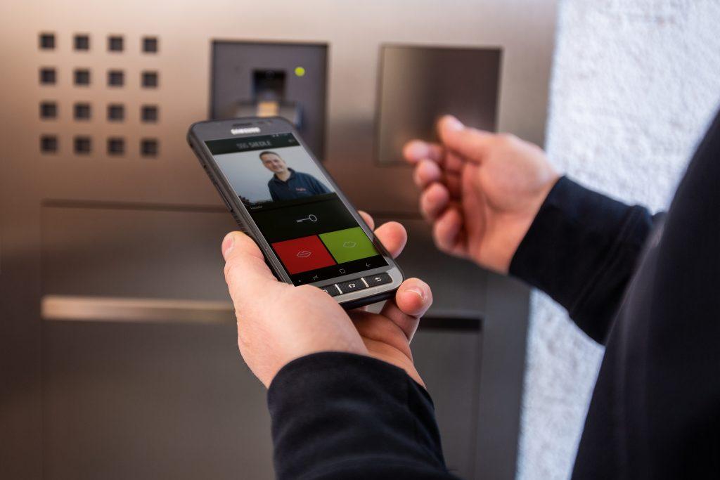 Die Siedle App für iOS und Android verfügt über eine klar gestaltete Benutzeroberfläche mit Sicherheitsabfrage. Erst wenn der virtuelle Schlüssel durch Wischen ins Türschloss gezogen worden ist, öffnet die Haustür. (Bild: S. Siedle & Söhne)
