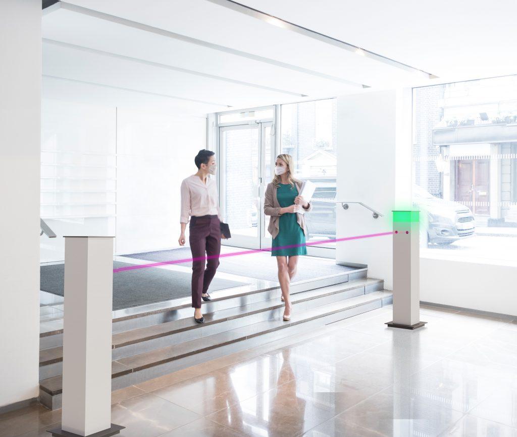 Two female professionals in modern foyer walking to office. Businesswomen talking on way to work in bright naturally lit modern office interior. (Bild: Deutsche Telekom IoT GmbH)