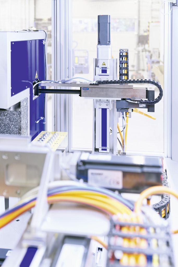 Mithilfe der kompakten ELS-Auslegerachse werden die Teile aus der Reinigungskabine entnommen und dem folgenden Präge- und Prüfprozess zugeführt.