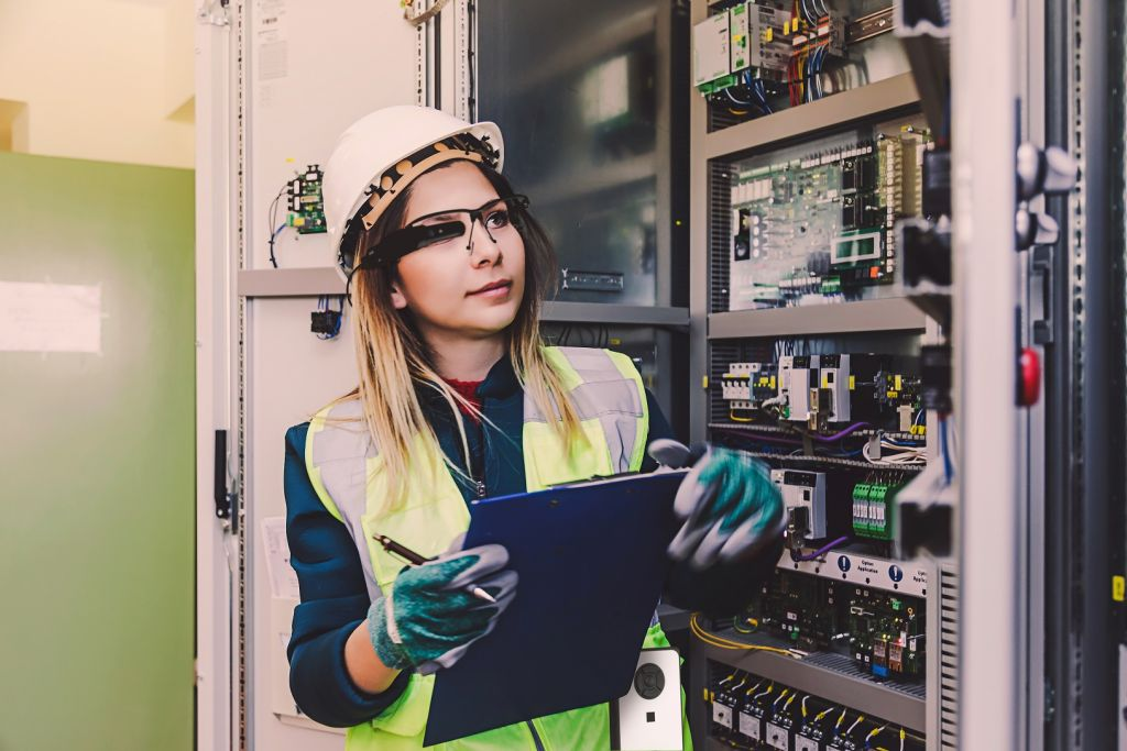 Young woman industrial service engineer wearing white worker headwear standing, working, checking conducts a safety check front of a control panel read and writing notes about technical problems in boiler energy control room of modern thermal or nuclear p