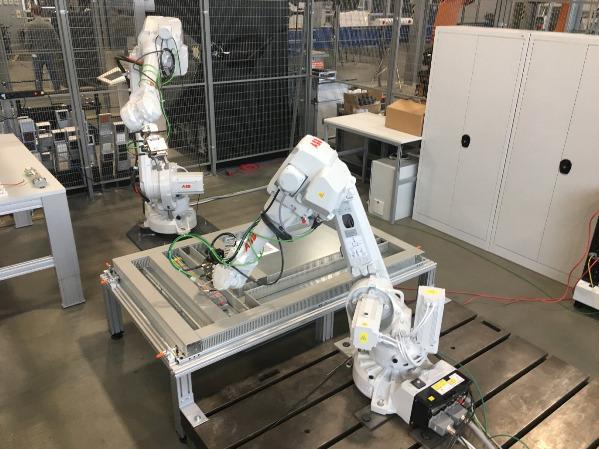Zur Validierung der Ergebnisse wurde für das Projekt Roboschalt an der Ruhr-Universität Bochum eine Versuchszelle, bestehend aus zwei Industrierobotern von ABB, aufgebaut. (Bild: Lehrstuhl für Produktionssysteme, Ruhr-Universität Bochum)