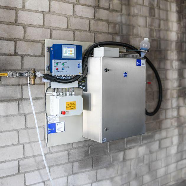 Per schwarzem Hygieneschlauch wird das Prozesswasser automatisch dem INWATROL L.nella+-System mit seinem Messreaktor im Edelstahl-Schaltschrank zugeführt. Links die übersichtliche Steuereinheit und der Klemmkasten.