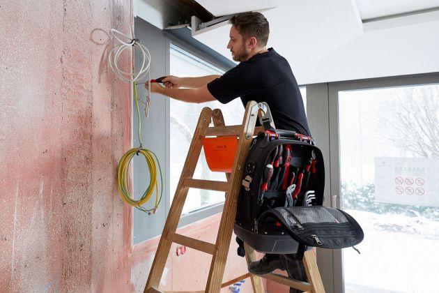 Ein Haken zum Aufhängen des Rucksacks ermöglicht bei erhöhten Arbeiten, wie z.B. auf Leitern, komfortableres Arbeiten und eine erleichterte Werkzeugentnahme.