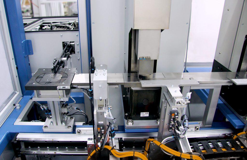 Im ersten Schritt schiebt und positioniert ein Schlitten die Feder unter die erste Servopresse der Baureihe aiPress. Diese belastet die Feder mit einer erforderlichen Kraft, um sie in eine definierte Form zu bringen.