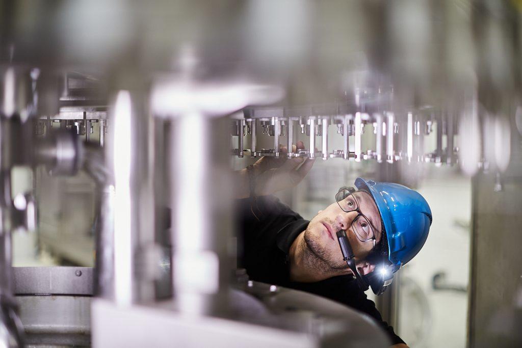 Ein Mitarbeiter von Krones inspiziert die Flaschenabfüllanlage.