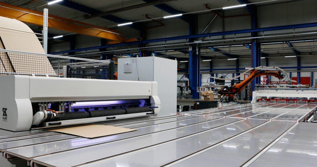 Der Kraft-Kartonschneideautomat VPS100 stellt die passgenauen Kartons für die Werkstücke her. Die Maschine bedient sich vollautomatisch aus dem Rohpappenspeicher und wählt die entsprechende Pappe mit dem geringsten Verschnitt für das Werkstück aus.