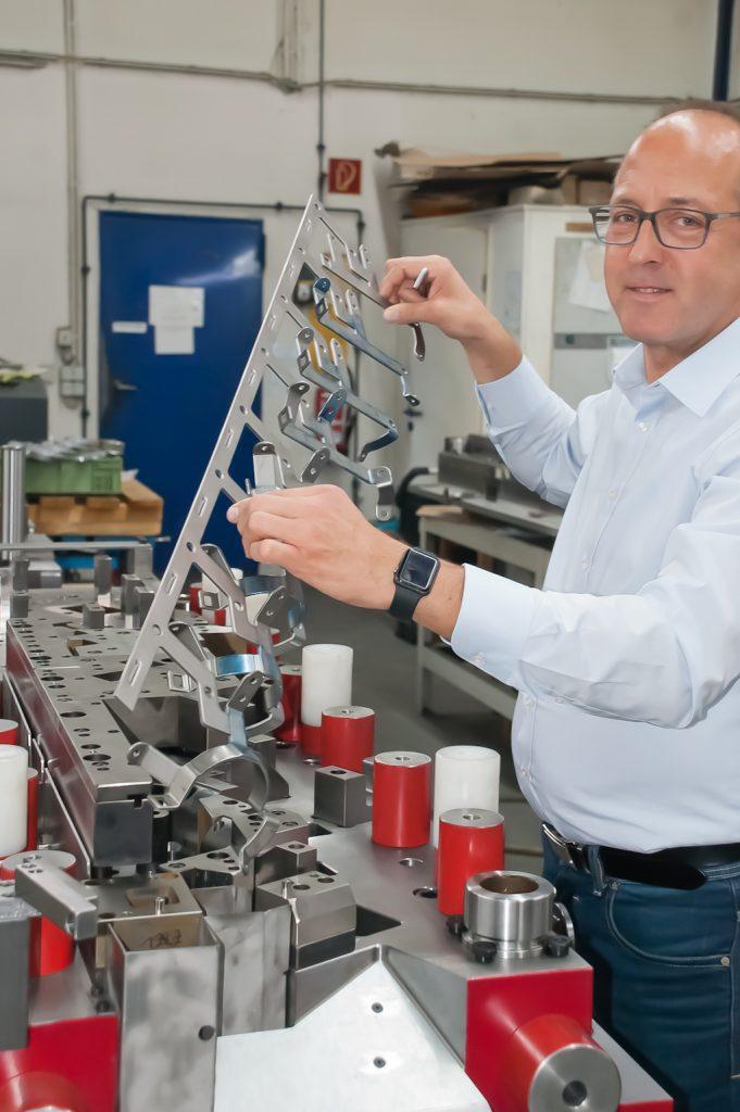 Eine Hälfte des fertig montierten Folgeverbundwerkzeugs für einen Halter: Firmenchef Frank Ebel hält den dazugehörenden Teststreifen in der Hand.