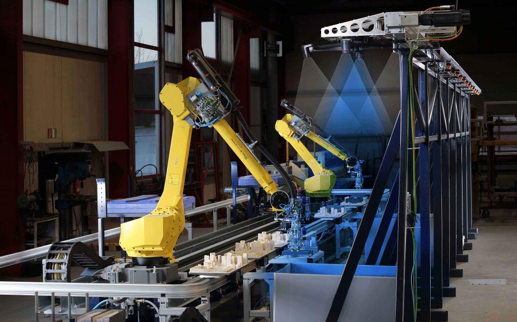 Bei Tür- und Torspezialist Hörmann entnehmen zwei Fanuc-Roboter mit Vision-System auf einer Linearachse die Produktkomponenten aus Großladungsträgern.