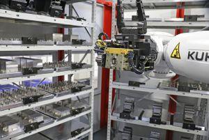 Ein Roboter versorgt das 5-Achs-Bearbeitungszentrum mit vorgerüsteten Werkstückpaletten.